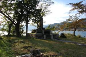 背後から夕陽をあびる海津の忠魂碑